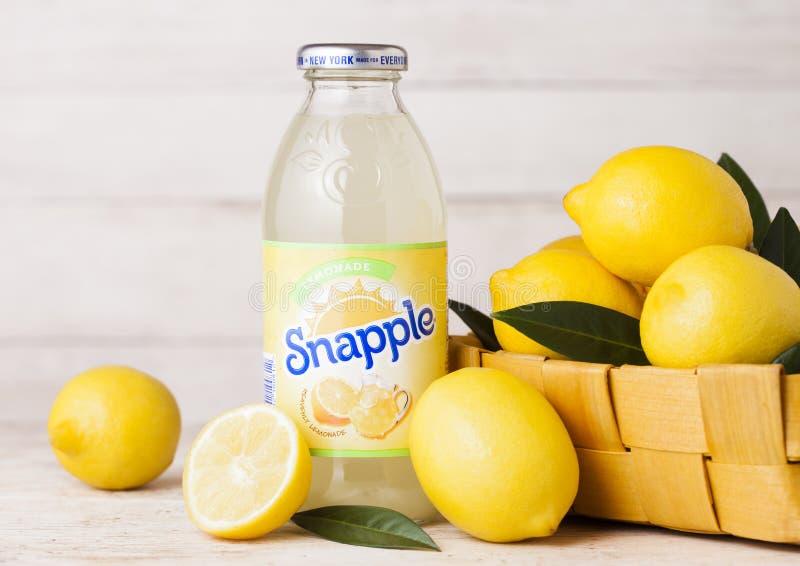 伦敦,英国- 2018年9月03日:瓶Snapple在木背景的柠檬汁用在竹篮子的新鲜的柠檬 Snapple是 库存图片