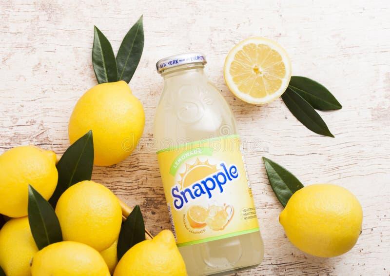 伦敦,英国- 2018年4月27日:瓶Snapple在木背景的柠檬汁用新鲜的柠檬 Snapple是博士的产品 图库摄影
