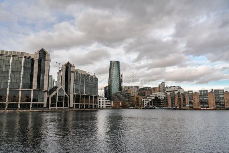 伦敦,英国- 2019年3月05日:舱内甲板和房子沿金丝雀码头银行,监督河边公寓 图库摄影