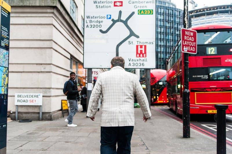 伦敦,英国- 2018年11月20日:走在有路牌的街道的老伦敦人商人与在许多的箭头 免版税图库摄影