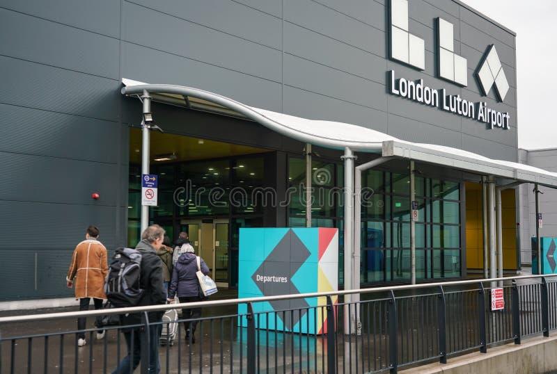 伦敦,英国- 2019年2月05日:进入卢顿机场的离开大厅乘客在阴暗天 LTN是第5 免版税库存图片