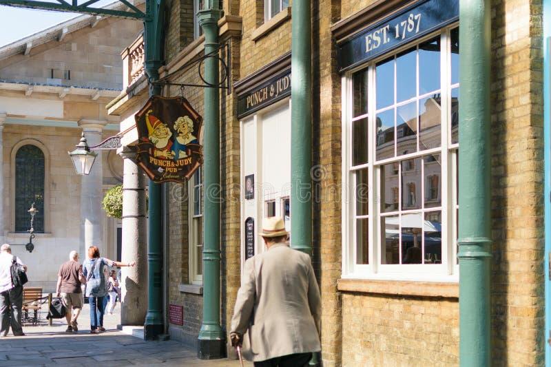 伦敦,英国- 2016年8月30日:一个未认出的人步行在Covent市场上通过拳打&茱蒂客栈 客栈在1787年被修造了 免版税库存图片