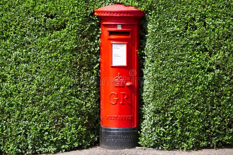 伦敦,英国/英国- 2019年7月13日:皇家在绿色树篱灌木掩藏的邮件红色柱子邮箱 免版税图库摄影