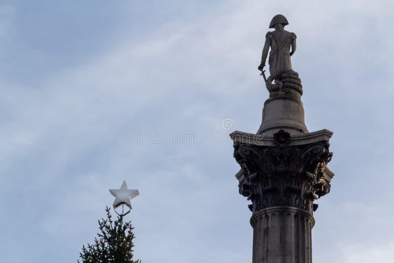 伦敦,英国- 17,2018年12月:圣诞树斯塔尔和纳尔逊海军上将著名雕象特拉法加广场的在伦敦,英国 库存图片
