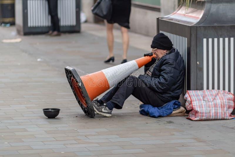 伦敦,英国- 17,2018年12月:坐街道在一次性杯子附近和举行明亮的橙色交通的一个男性叫化子的侧视图 免版税库存图片
