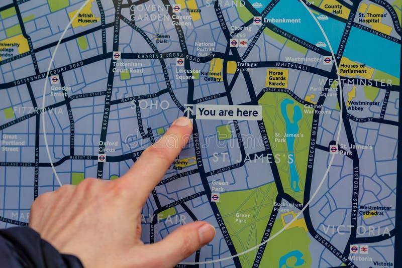 伦敦,英国- 17,2018年12月:旅游看看伦敦和展示地图由他现在的手指 伦敦有  免版税图库摄影