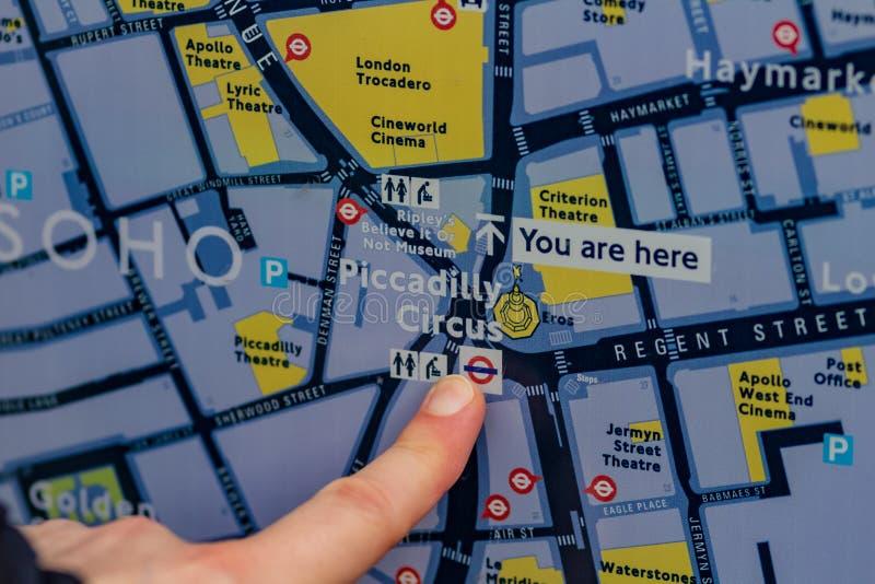 伦敦,英国- 17,2018年12月:旅游看看伦敦和展示地图由他现在的手指 伦敦有  库存照片