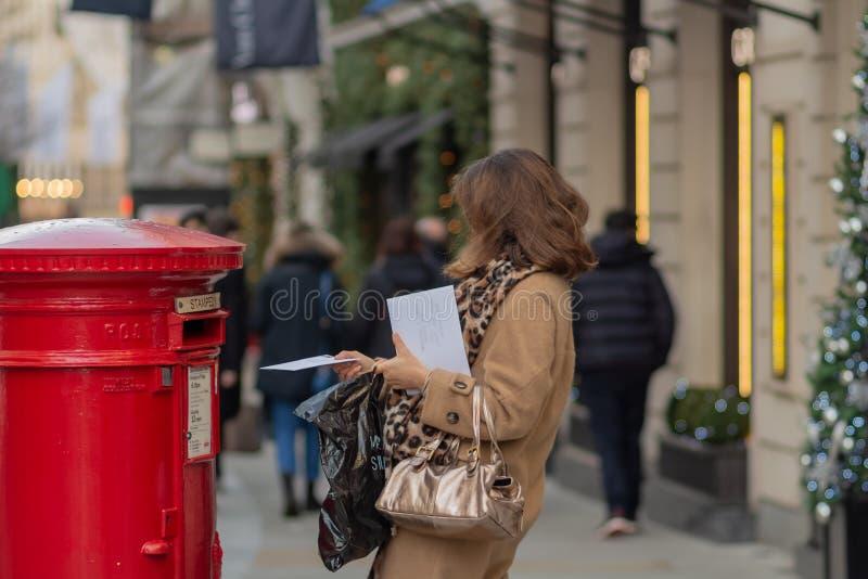 伦敦,英国- 17,2018年12月:妇女在红色传统维多利亚女王时代的英国邮箱身分的托人由一地带到另一地的邮件在伦敦 库存照片