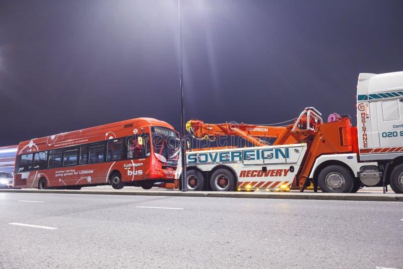 伦敦,英国- 2016年 03 02 :红色公共汽车o一辆拖车在伦敦 库存图片