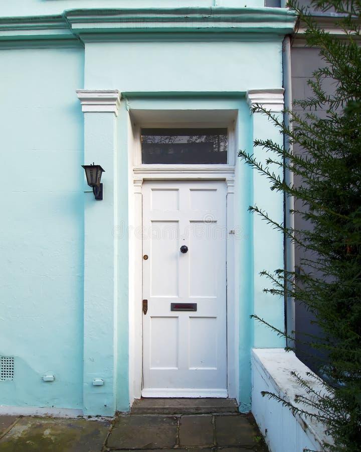 伦敦,诺丁山,与白色门的葡萄酒房子浅兰的前面 免版税库存图片