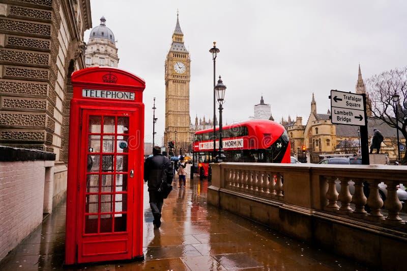 伦敦, UK-FEBRUARY 12 :传统红色电话亭在与大本钟和红色公共汽车的雨天在背景中 库存照片