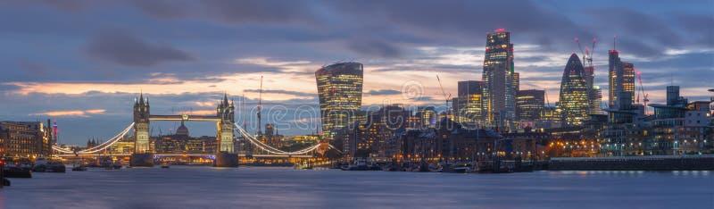 伦敦-塔桥梁、河沿和摩天大楼的全景黄昏的与剧烈的云彩 免版税图库摄影