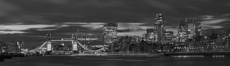 伦敦-塔桥梁、河沿和摩天大楼的全景黄昏的与剧烈的云彩 免版税库存照片
