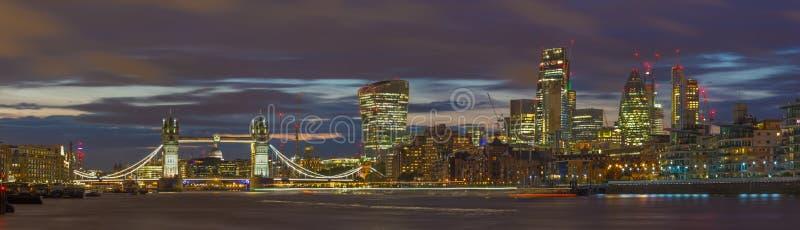 伦敦-塔桥梁、河沿和摩天大楼的全景黄昏的与剧烈的云彩 图库摄影