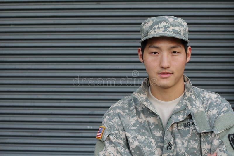 伪装的亚裔士兵与在制服的美国旗子 库存图片