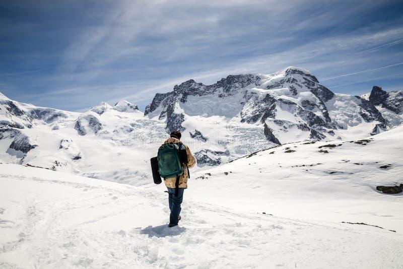 伪装站立在雪山前面背景的冬天外套和背包的一个人  图库摄影
