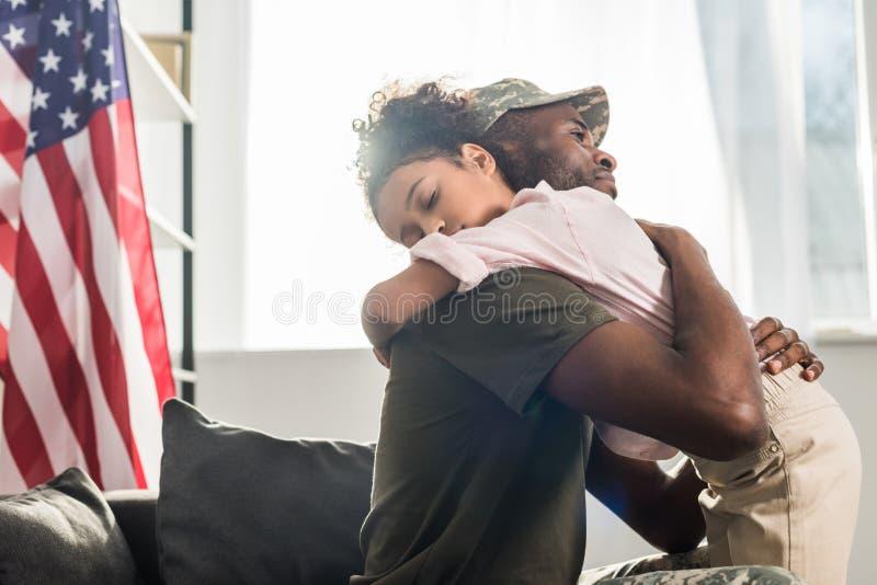 伪装衣裳和她女儿拥抱的男性战士 库存照片