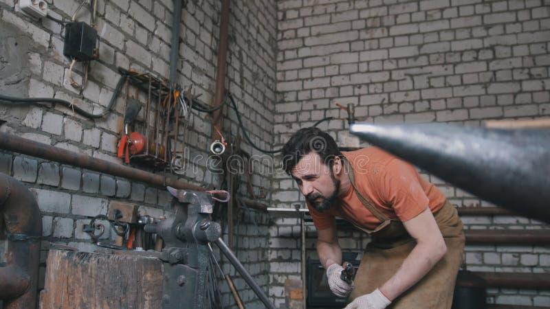 伪造的肌肉铁匠在金属铁砧附近 库存照片