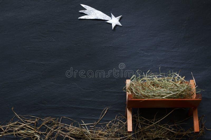 伯利恒abstracy圣诞节背景在黑大理石的诞生场面饲槽和星  免版税库存照片