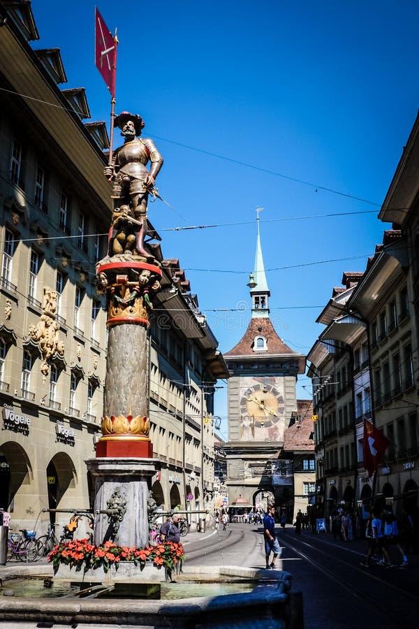 伯尔尼,瑞士- 2017年5月26日:一个美丽的喷泉和著名天文学钟楼在中世纪市伯尔尼 免版税库存图片