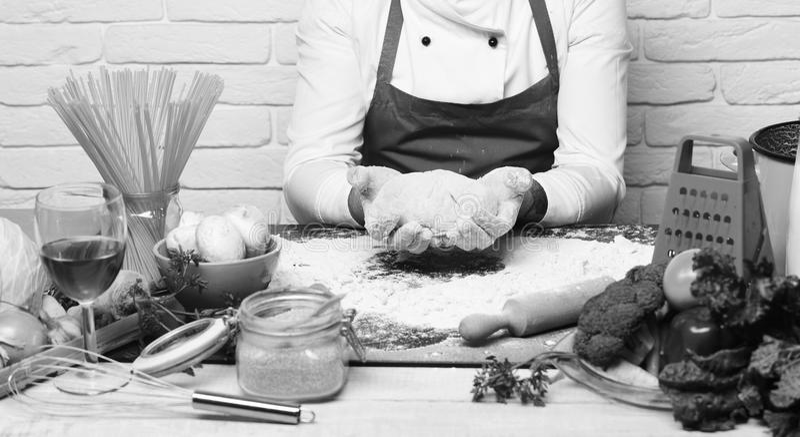 伯根地制服的厨师由与菜和厨具的桌坐 男性手工用在白色的被揉的面团 库存照片