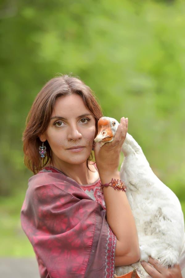 伯根地礼服的妇女在有鹅的一个农场 图库摄影