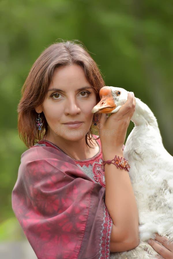 伯根地礼服的妇女在有鹅的一个农场 库存图片