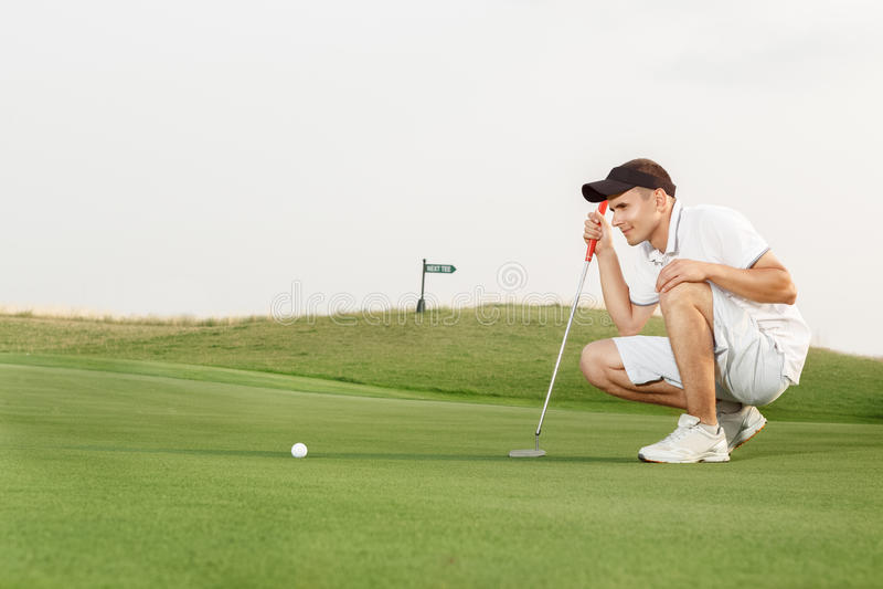 估计他的选择的高尔夫球运动员对轻轻一击 免版税库存图片