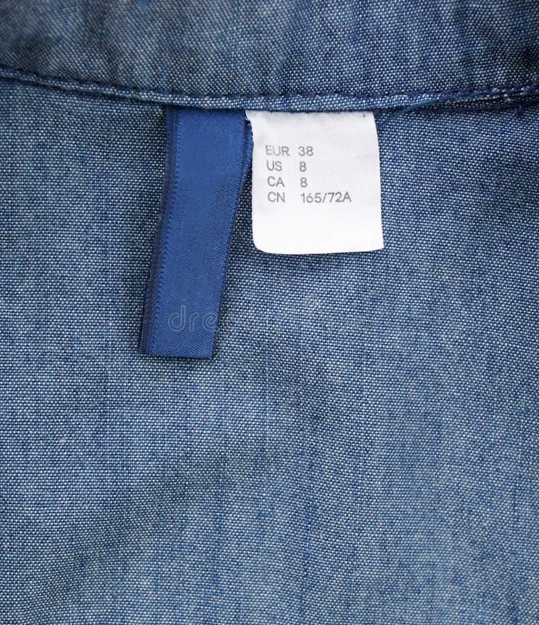 估量在牛仔裤衬衣和白色标记的标签 免版税库存照片