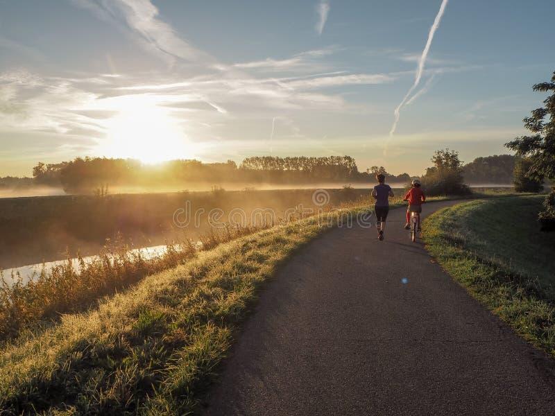 伴随他的清早奔跑的循环的年轻儿子母亲 图库摄影