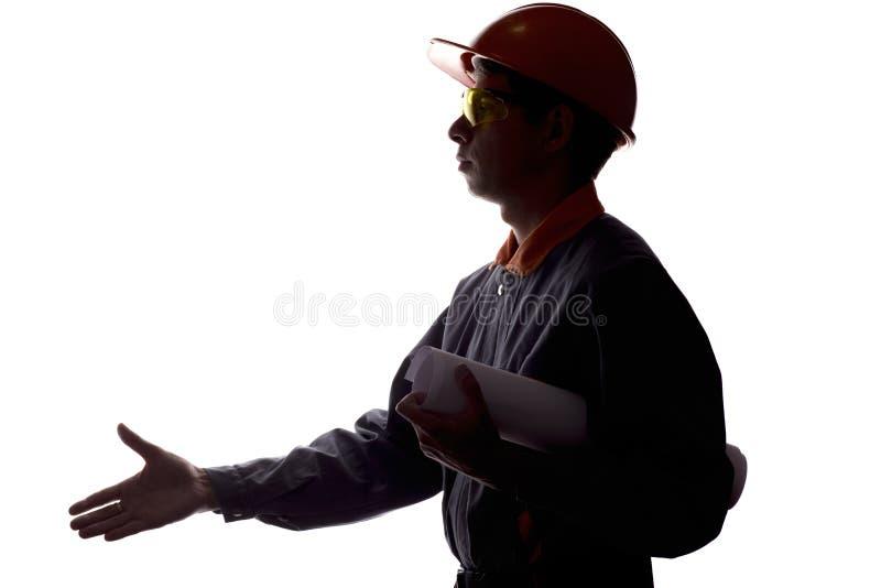 伸他的握手的一名年轻建筑工人的剪影手在合同,总体的一个人的标志在a 免版税库存照片