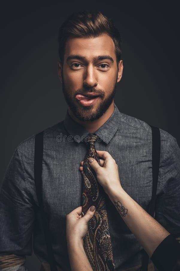 伸出他的舌头的年轻有胡子的人,当女性手调整时 库存照片