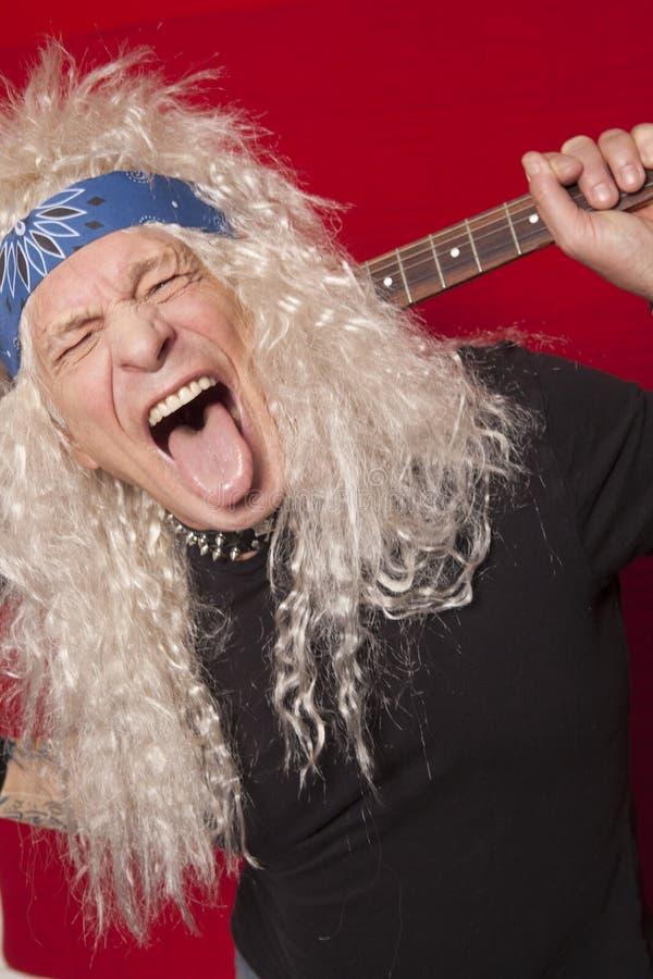 伸出在色的背景的中年男性吉他弹奏者特写镜头舌头 库存照片