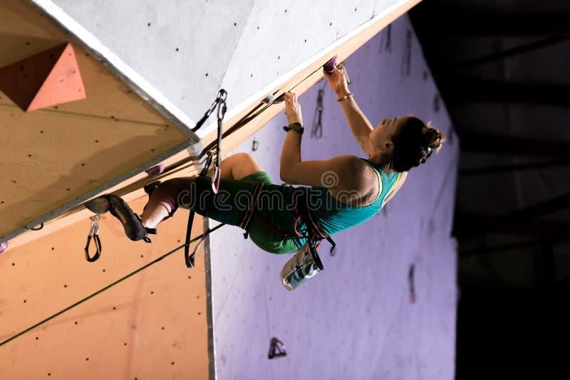伸出的屋顶的女性登山人在夜照明 库存照片