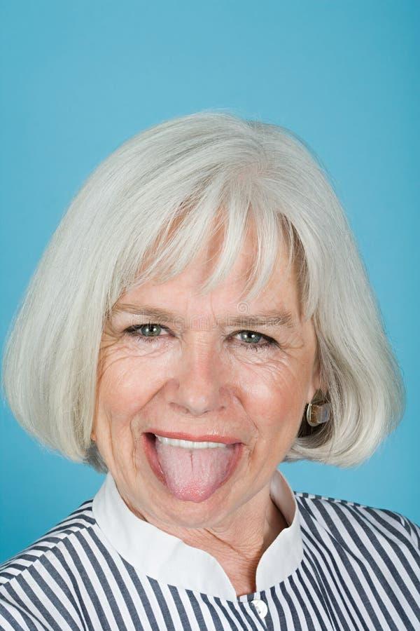 伸出舌头妇女 免版税库存图片