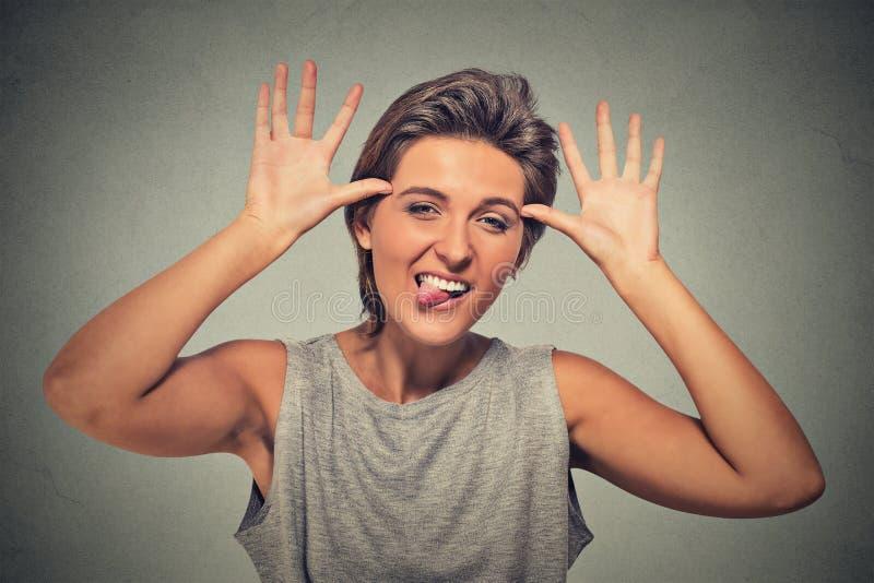 伸出舌头的年轻,幼稚,愚蠢粗鲁的妇女  库存图片
