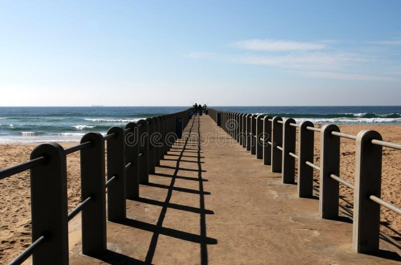 延伸到海滩的印度洋的具体码头 图库摄影