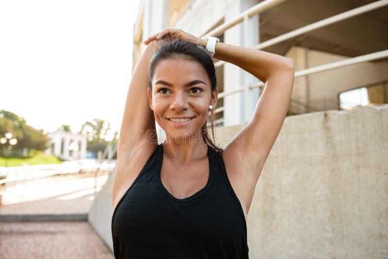 伸她的手的一个亭亭玉立的健身女孩的画象 库存图片