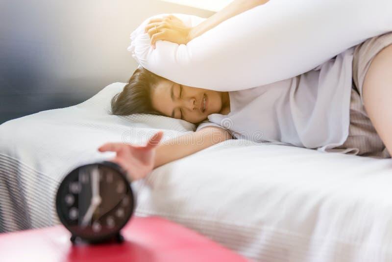 伸她的手的女性对敲响的警报关闭闹钟,妇女不喜欢得到被注重的早早醒 免版税库存图片
