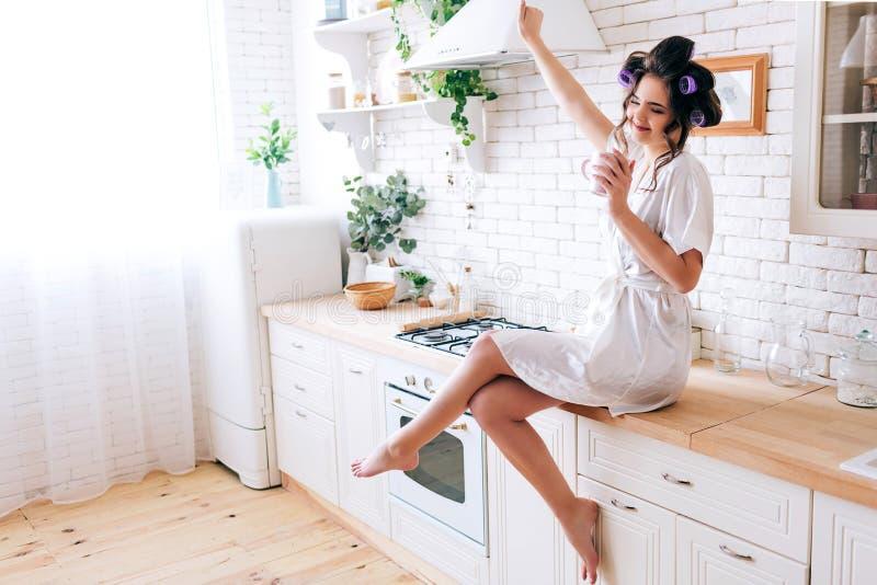 伸手和享有生活的年轻粗心大意的主妇 在手中举行杯子 在头发的卷发的人 单独在厨房里 免版税库存图片