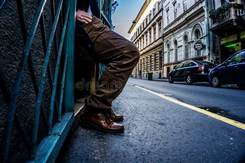 伸进他的在布达佩斯,有empasizing行动的测深索的匈牙利街道上的口袋的一个人的腿和手  库存图片