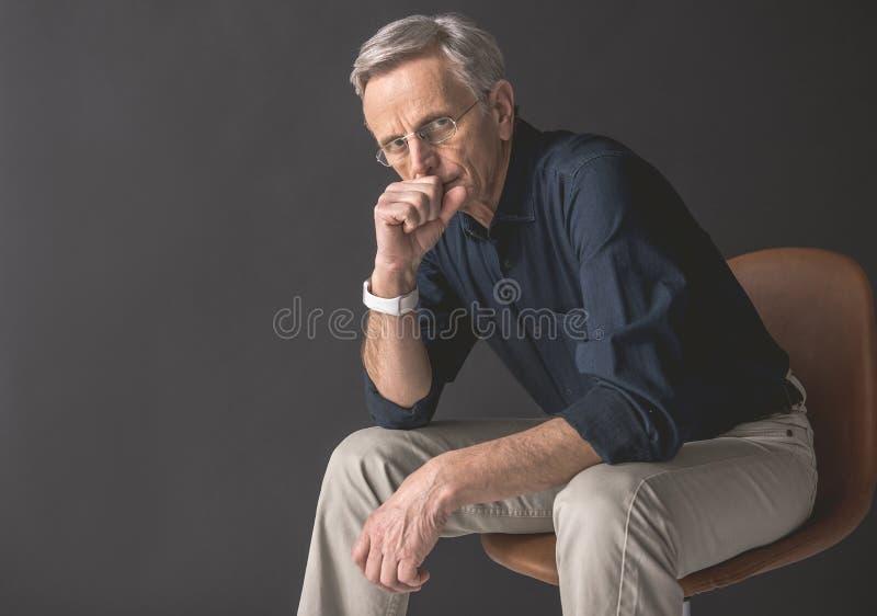 位于位子的沉思老人 免版税库存照片
