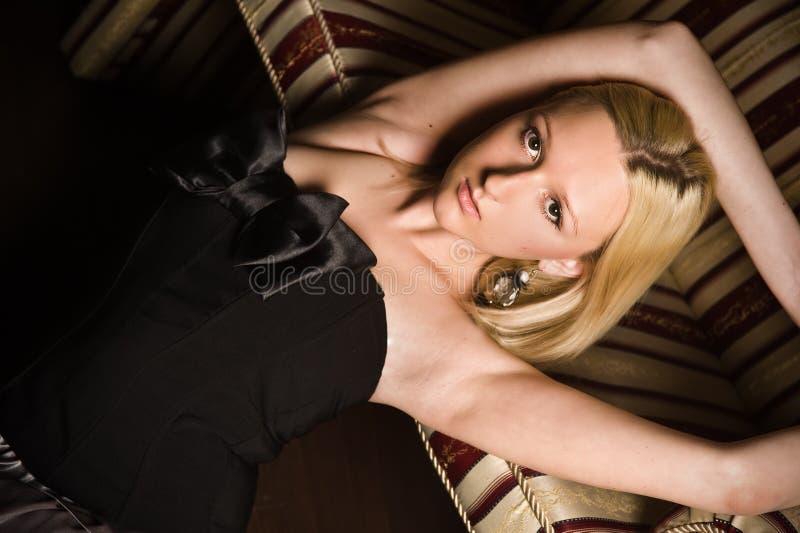位于在一个皮革沙发的美丽的妇女 免版税库存照片