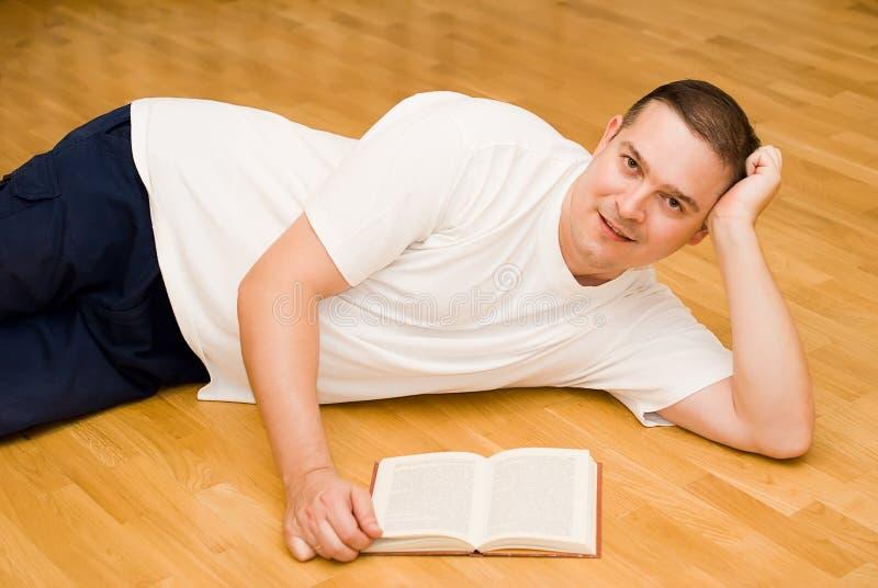 位于在与书的楼层上的年轻人 图库摄影