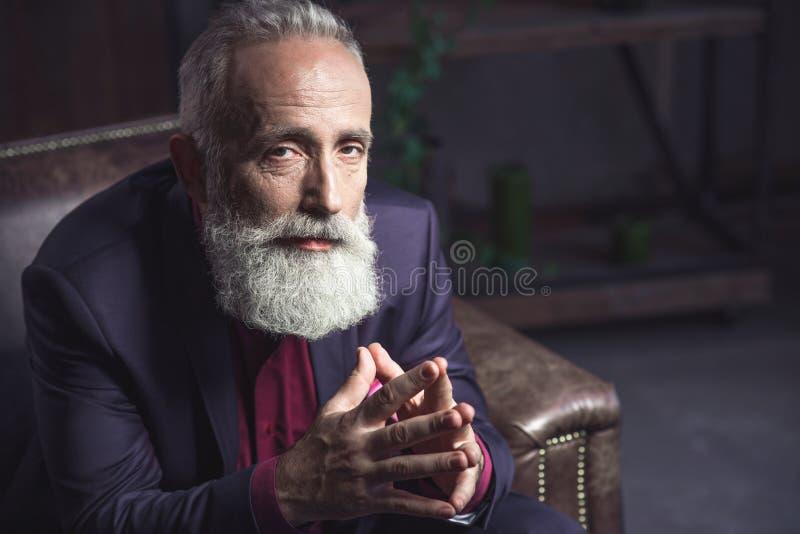 位于在公寓的严肃的有胡子的领抚恤金者 图库摄影