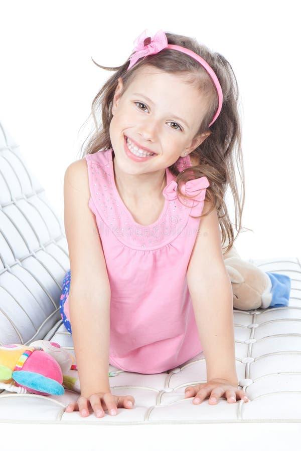位于在沙发的美丽的小女孩 库存图片