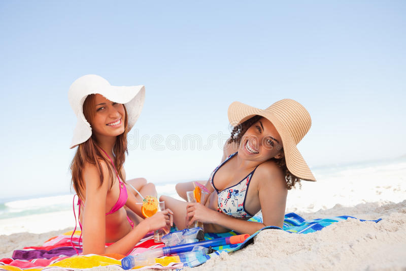 位于在海滩毛巾的新微笑的妇女 图库摄影