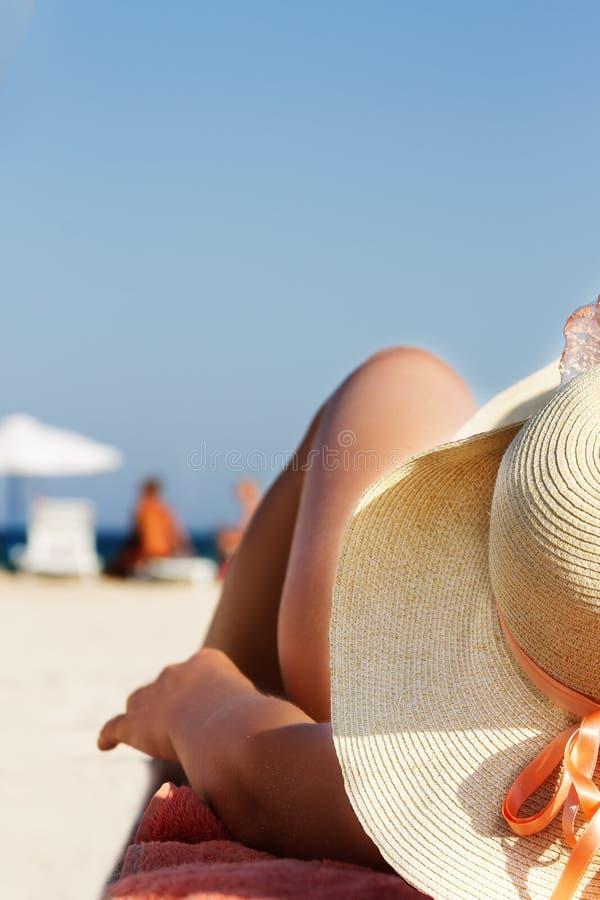 位于在海滩的帽子和比基尼泳装的妇女 图库摄影