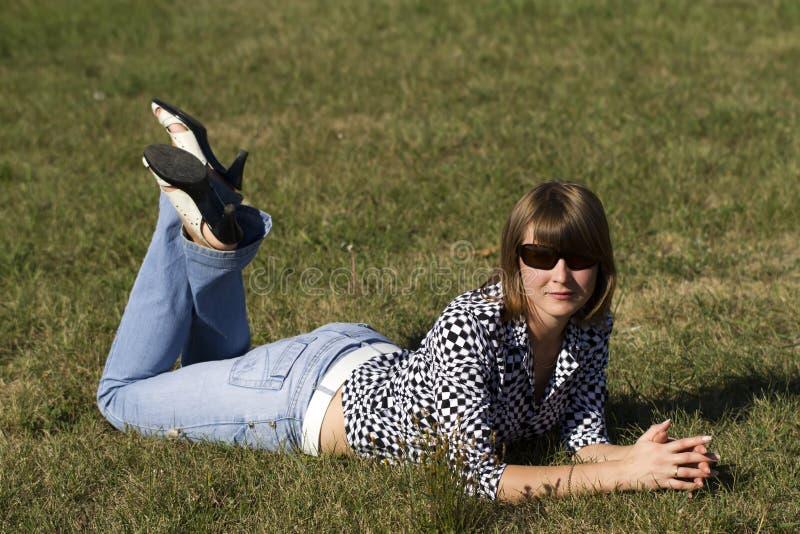 位于在草的妇女 免版税库存照片