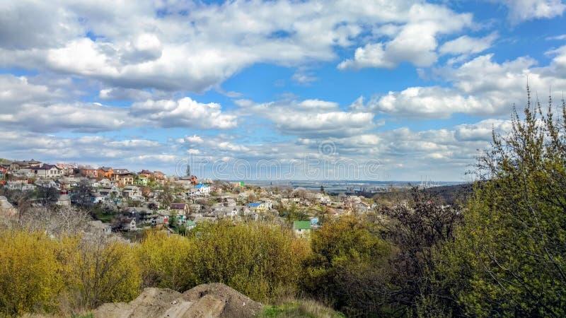 位于小山的许多小屋的城市视图 与许多的天空蔚蓝云彩 树和灌木在前景 免版税库存照片